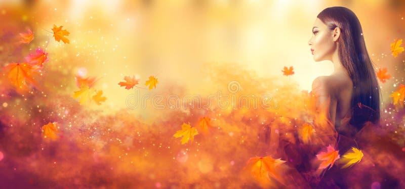 Schöne Frau, die in den Wald an einem Falltag geht Schönheitsmodefrau im Herbstgelbkleid lizenzfreie stockfotografie