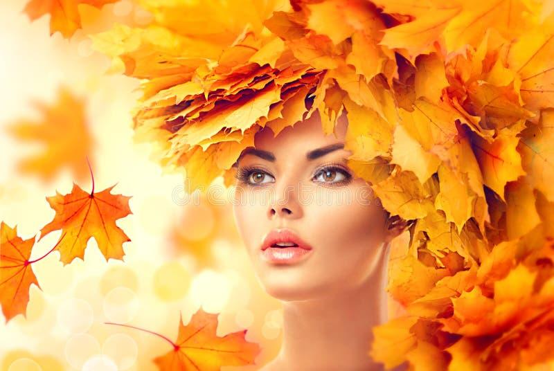 Schöne Frau, die in den Wald an einem Falltag geht Vorbildliches Mädchen der Schönheit mit heller Blattfrisur des Herbstes stockfoto