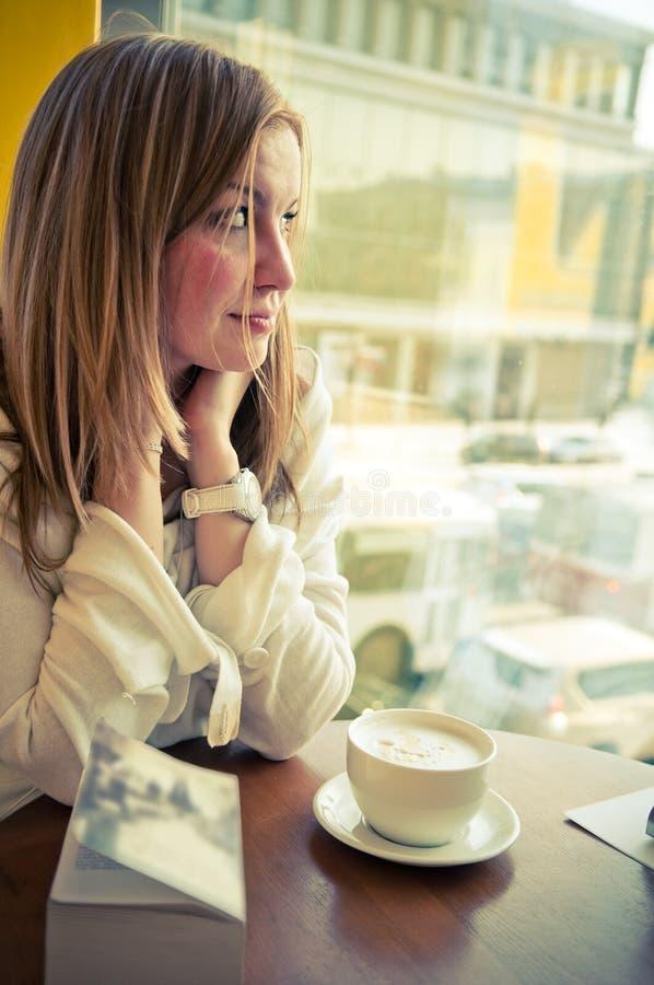 Schöne Frau, die durch ein Fenster schaut. lizenzfreie stockbilder
