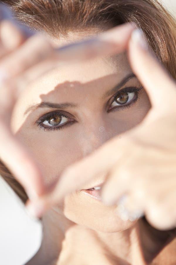 Schöne Frau, die durch ein Finger-Feld schaut stockfotografie