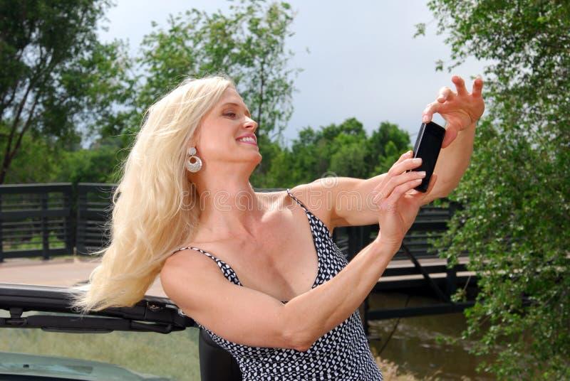 Schöne Frau, die ein Foto auf Ferien macht lizenzfreie stockfotografie