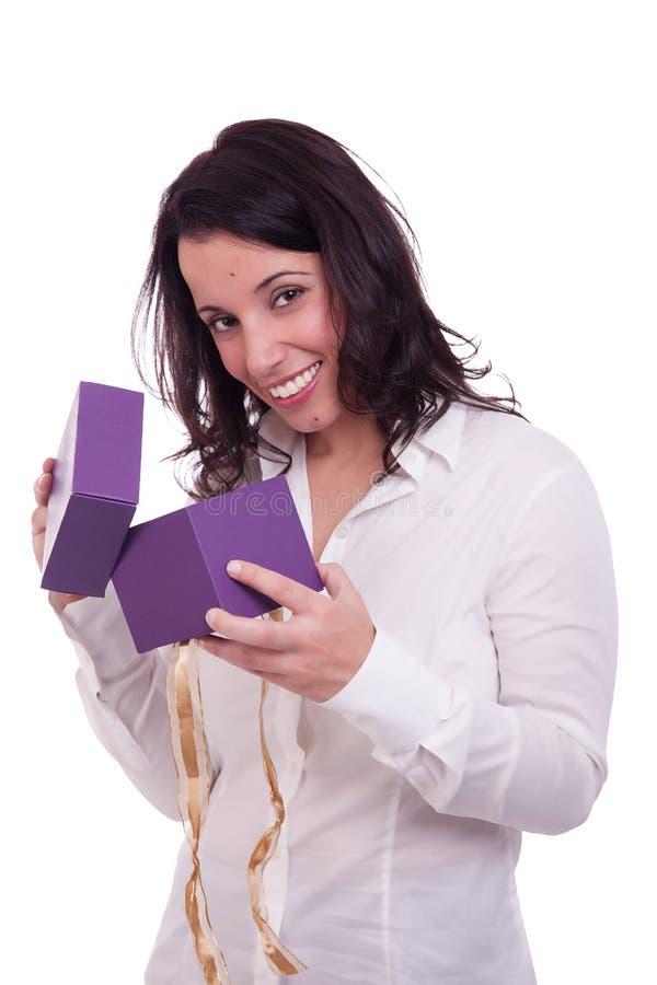Schöne Frau, die ein Geschenk öffnet lizenzfreie stockfotografie