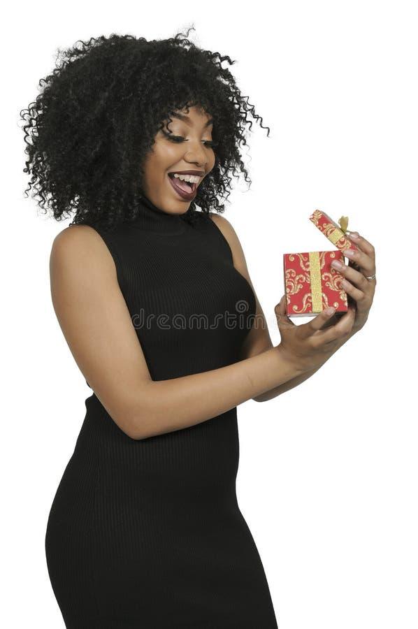 Schöne Frau, die ein Geschenk öffnet lizenzfreies stockfoto