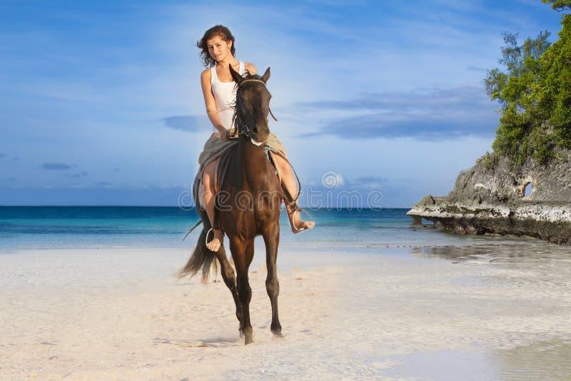 Schöne Frau, die ein Pferd auf tropischen Strand reitet stockbild