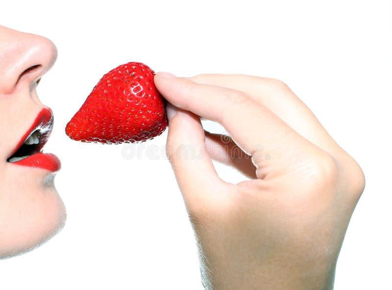 Schöne Frau, die eine Erdbeere isst lizenzfreie stockbilder