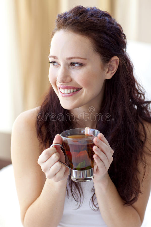 Schöne Frau, die eine Tasse Tee im Bett trinkt lizenzfreies stockbild