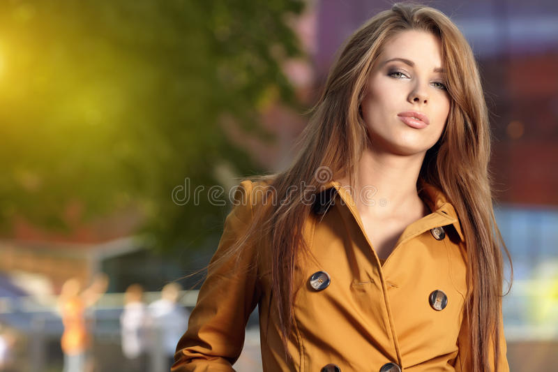 Schöne Frau, die in einem Park im Herbst steht lizenzfreie stockfotografie