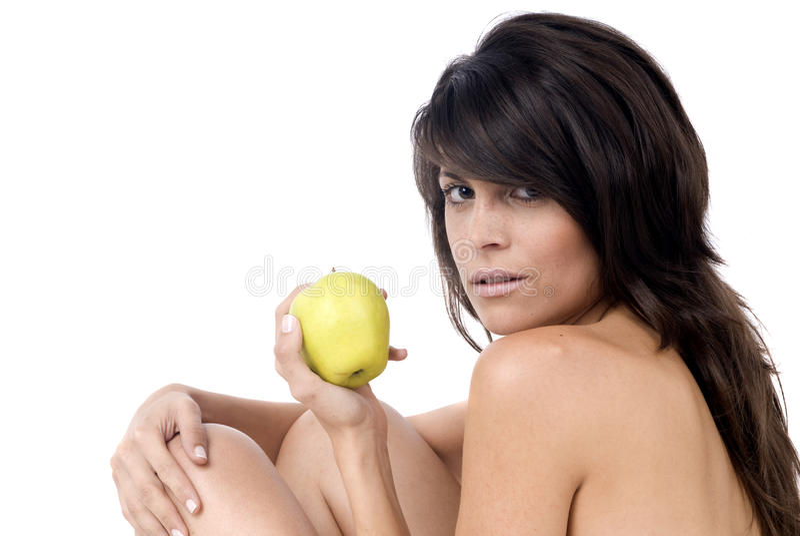Schöne Frau, die einen Apfel im Weiß isst stockfotografie