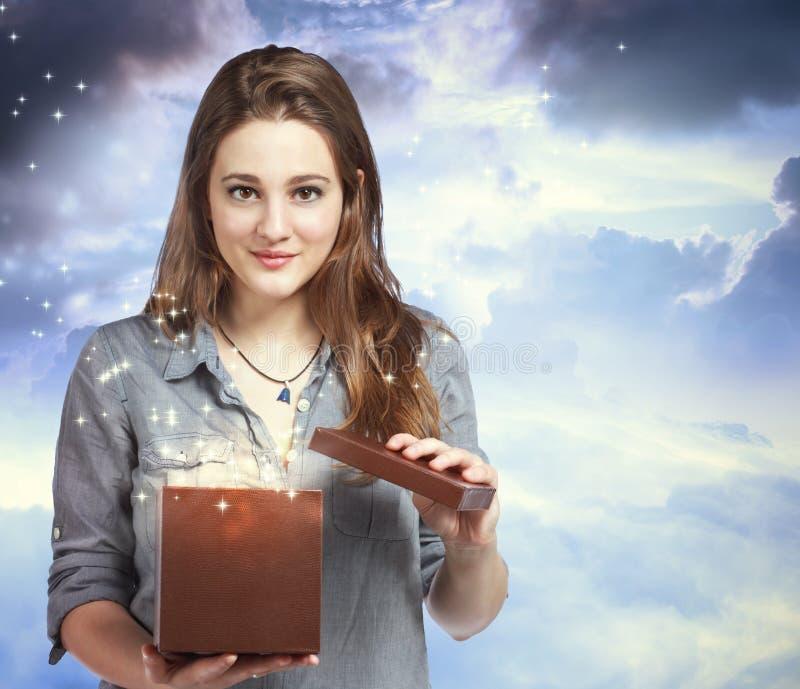 Schöne Frau, die einen Geschenk-Kasten öffnet lizenzfreie stockfotografie