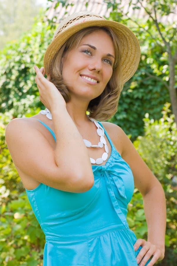 Schöne Frau, die einen Strohhut trägt stockbilder