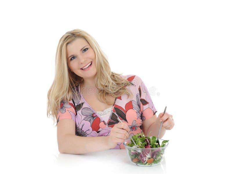 Schöne Frau, die Gemüsesalat isst stockfotografie