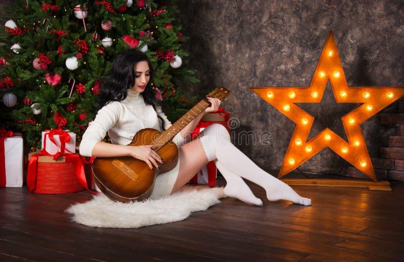 Schöne Frau, die Gitarre spielt Brunette Frau mit Gitarre am Weihnachten stockfotos