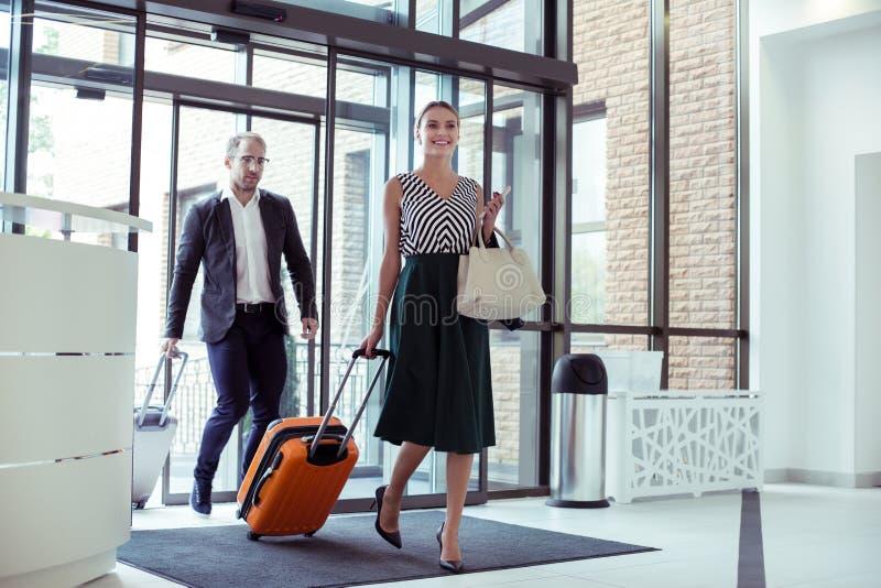 Schöne Frau, die ihren erfolgreichen Ehemann auf Geschäftsreise begleitet stockbild