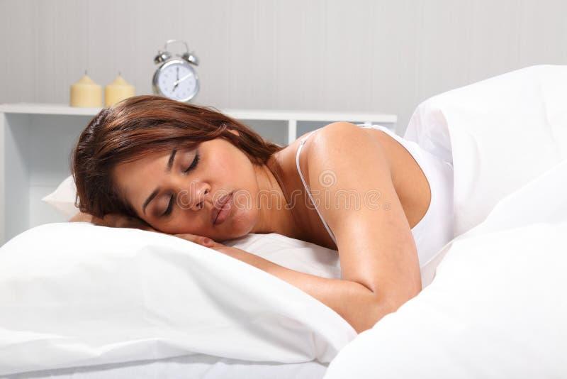 Schöne Frau, die im Bettkopf auf Kissen schläft stockfoto