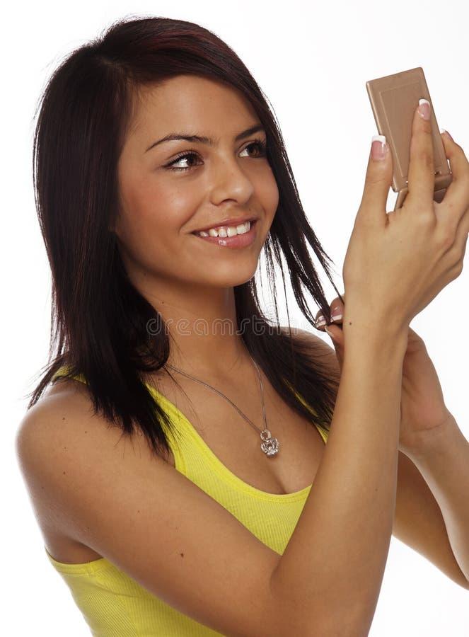 Schöne Frau, die im Spiegel sich überprüft stockfotografie