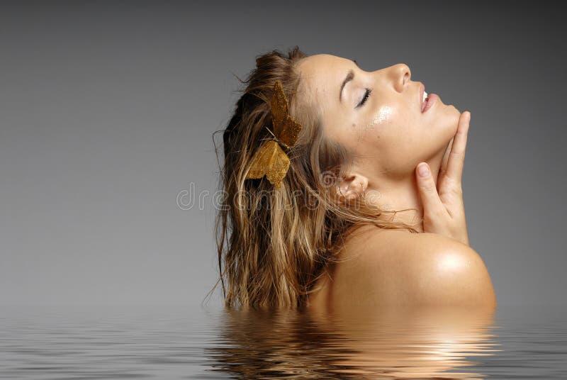 Schöne Frau, die im Wasser - Badekurort badet stockfoto
