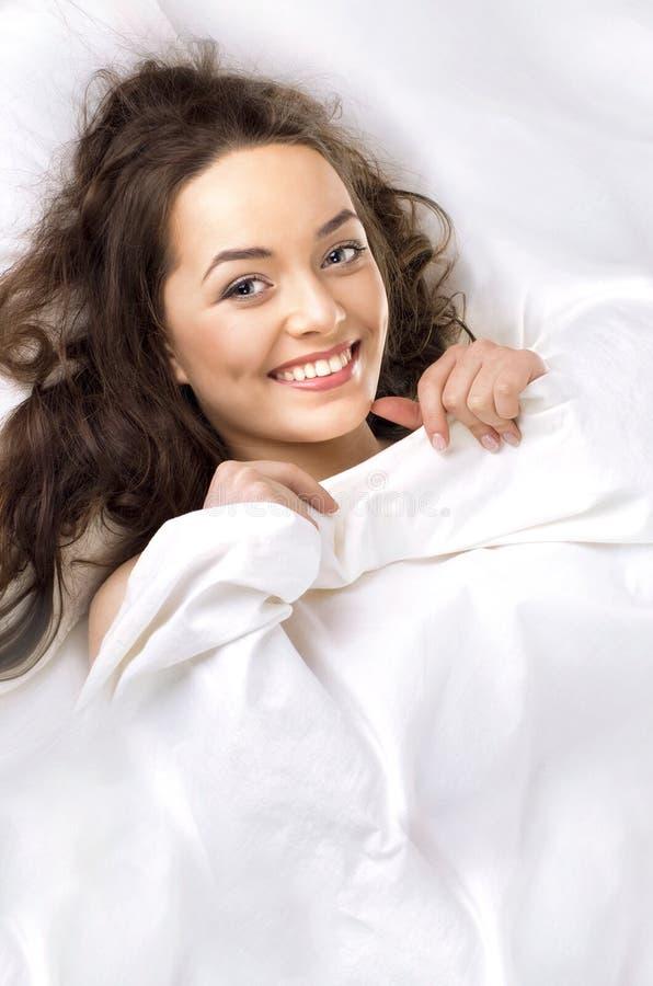 schöne Frau, die im weißen Bett schläft lizenzfreie stockfotos