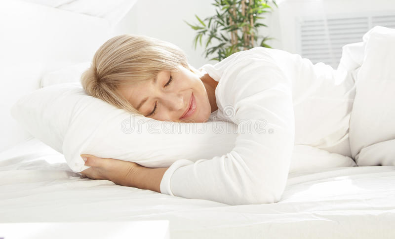 Schöne Frau, die im weißen Bett schläft lizenzfreies stockfoto