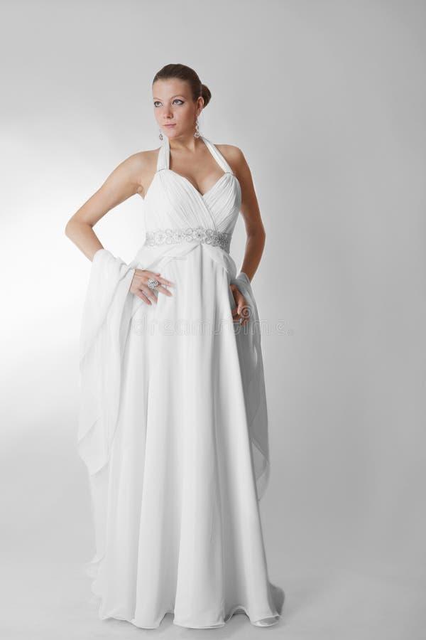 Schöne Frau, die luxuriöses Hochzeitskleid trägt stockfoto