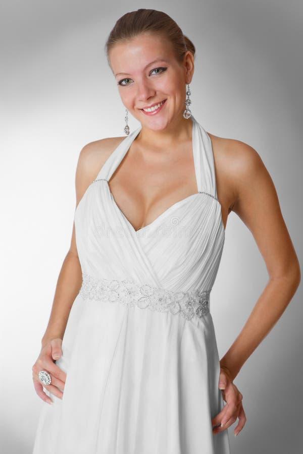 Schöne Frau, die luxuriöses Hochzeitskleid trägt stockbild