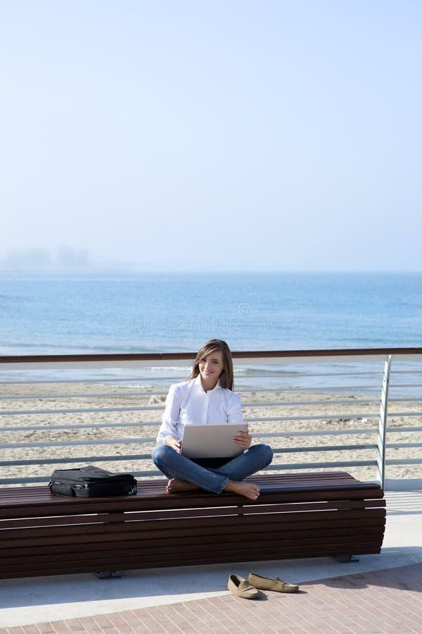 Schöne Frau, die mit dem Laptop im Freien arbeitet stockfoto