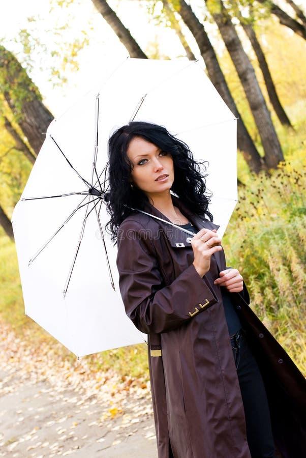 Schöne Frau, die mit einem Regenschirm geht stockfotos