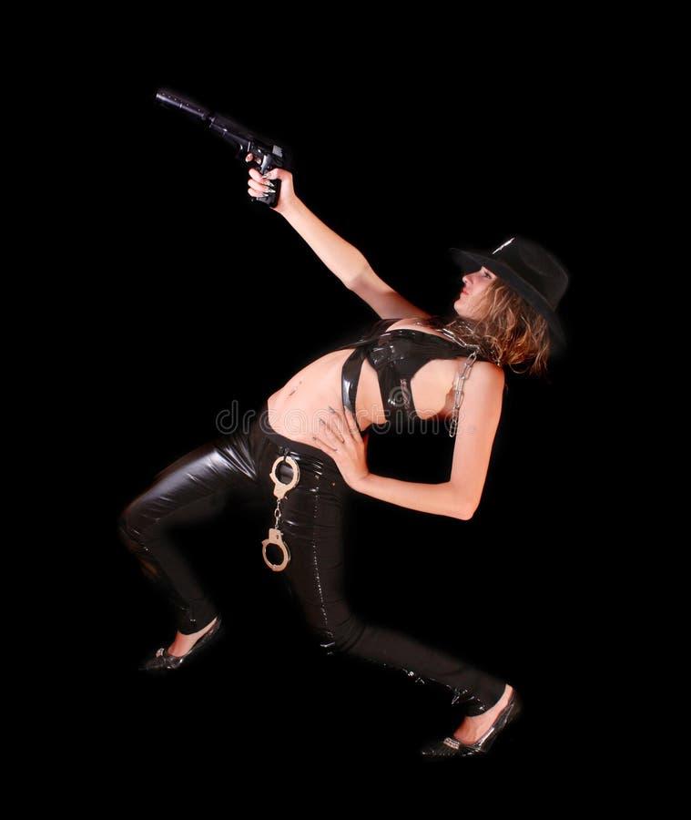 Schöne Frau, die mit Gewehr auf Schwarzem zielt lizenzfreie stockfotos