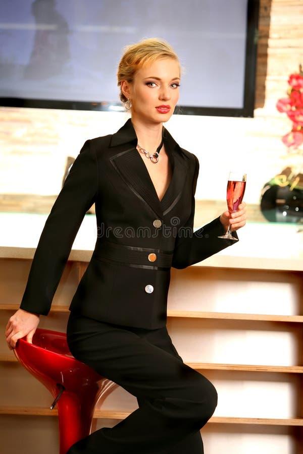 Schöne Frau, die rosafarbenen Wein am Stab trinkt stockfotografie