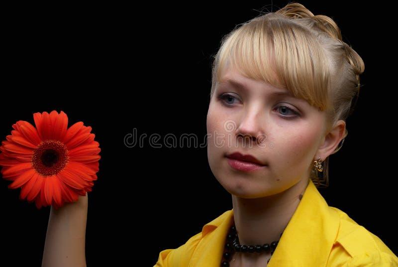 Schöne Frau, die rote Blume anhält lizenzfreie stockbilder