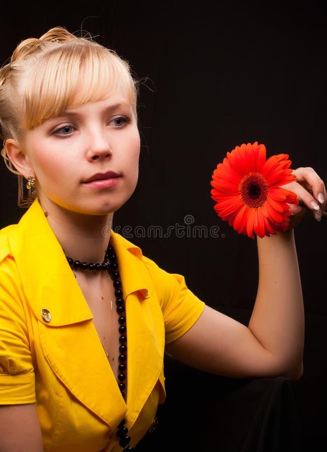 Schöne Frau, die rote Blume anhält stockfotografie