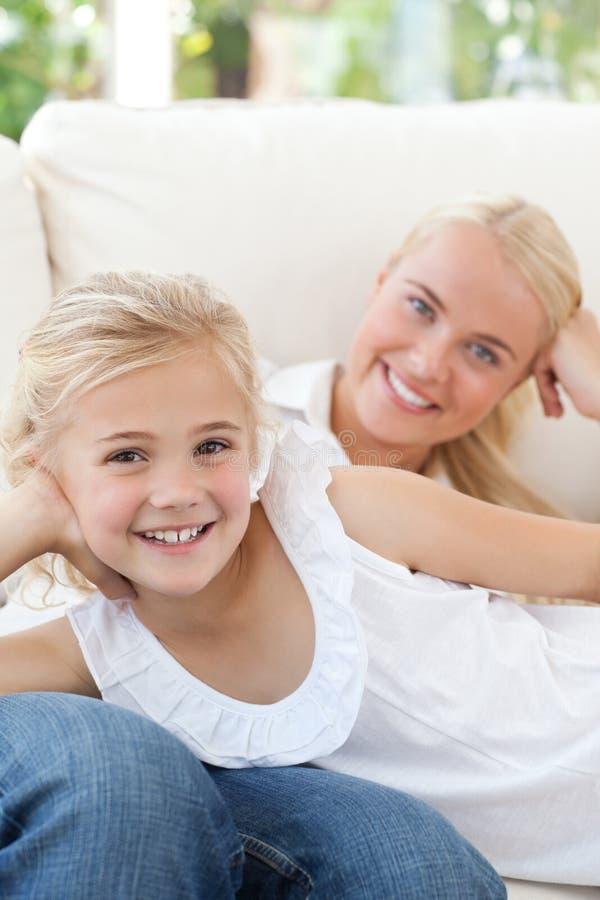 Schöne Frau, die sich mit ihrer Tochter hinlegt stockbild