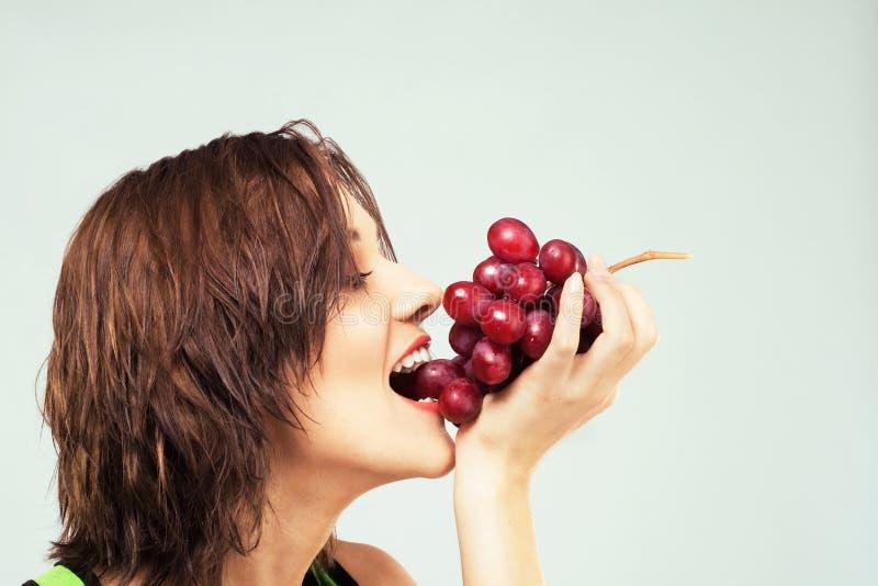 Schöne Frau, die Trauben isst stockfotos