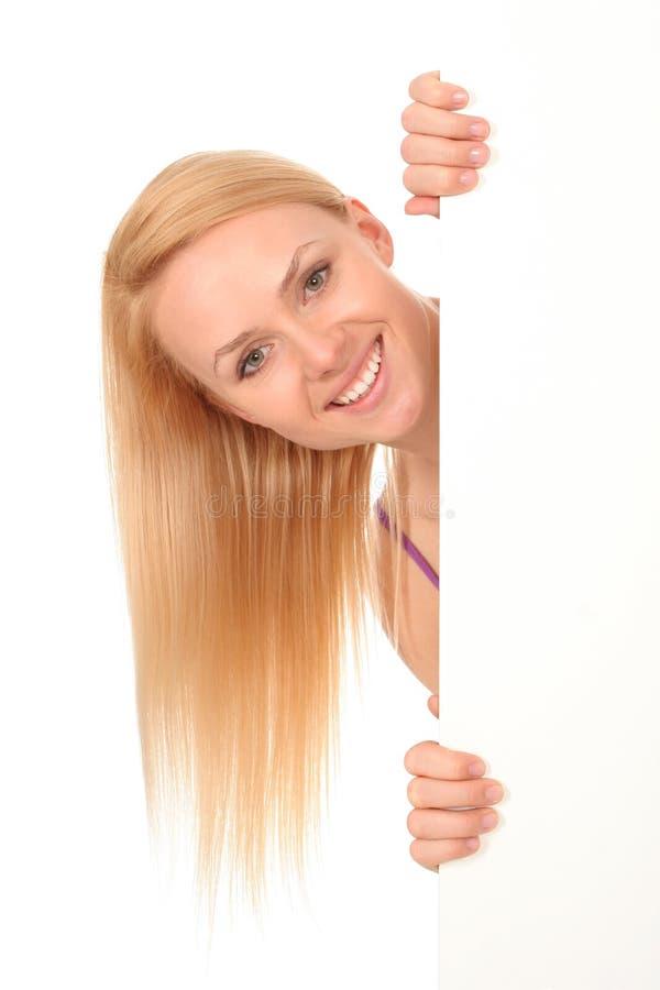 Schöne Frau, die unbelegtes Plakat anhält lizenzfreies stockfoto