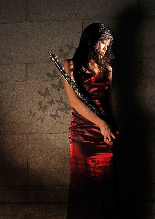Schöne Frau, die zum Musikinstrument anhält lizenzfreies stockfoto