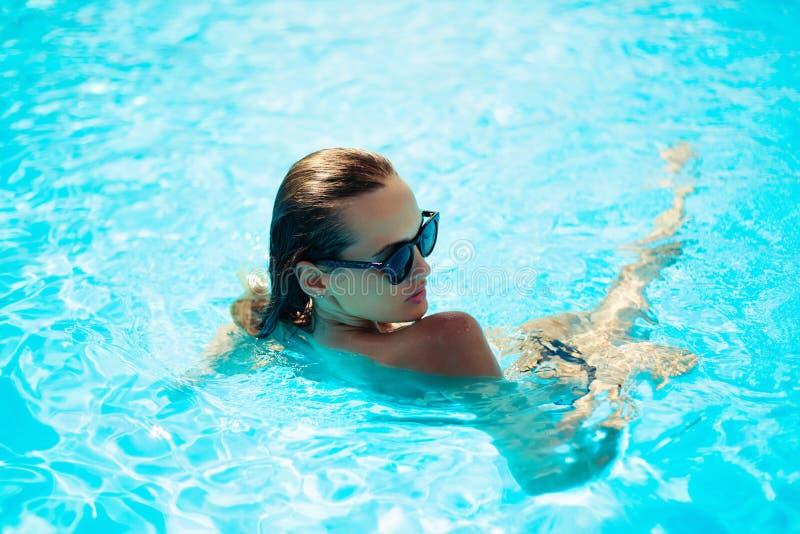 Schöne Frau in einem Swimmingpool lizenzfreie stockfotografie