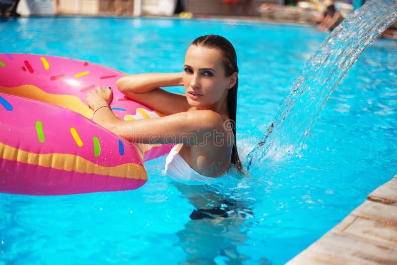 Schöne Frau in einem Swimmingpool stockbild