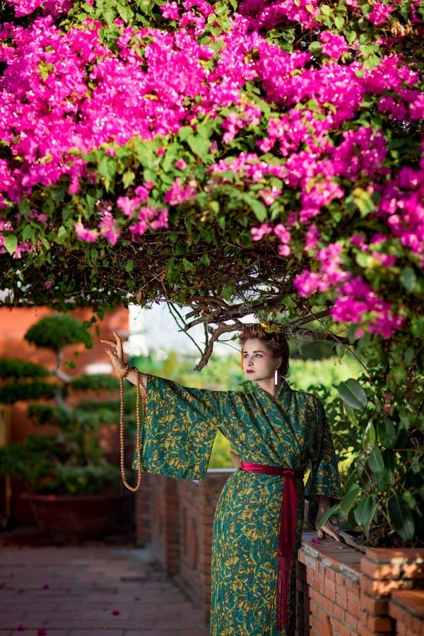 Schöne Frau in Geisha Kimono im Garten stockfotos