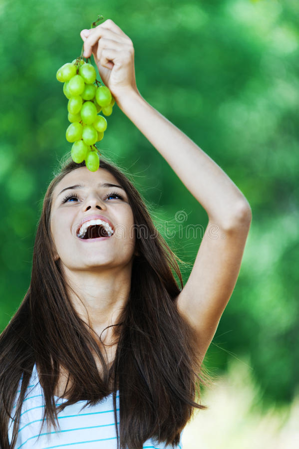Schöne Frau hält Trauben an lizenzfreie stockfotografie