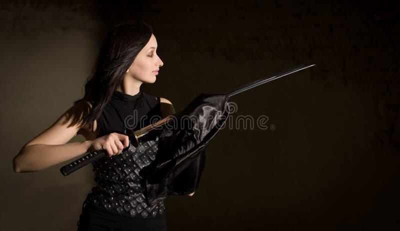 Schöne Frau im ledernen Kleidungsholdingsäbel lizenzfreies stockbild