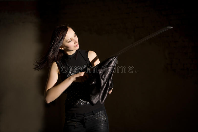 Schöne Frau im ledernen Kleidungsholdingsäbel lizenzfreies stockfoto