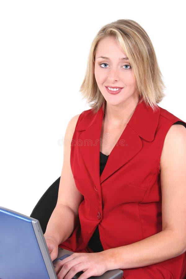 Schöne Frau im Rot auf Laptop lizenzfreie stockbilder