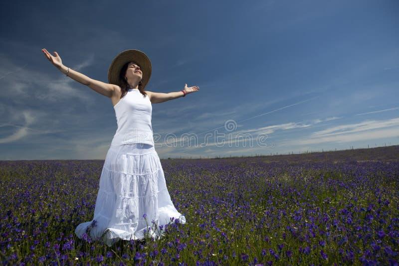 Schöne Frau im weißen Kleid mit den breiten Armen öffnen sich stockfotografie