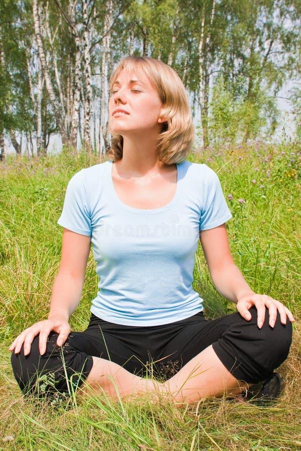 Schöne Frau meditiert auf der Natur stockfoto