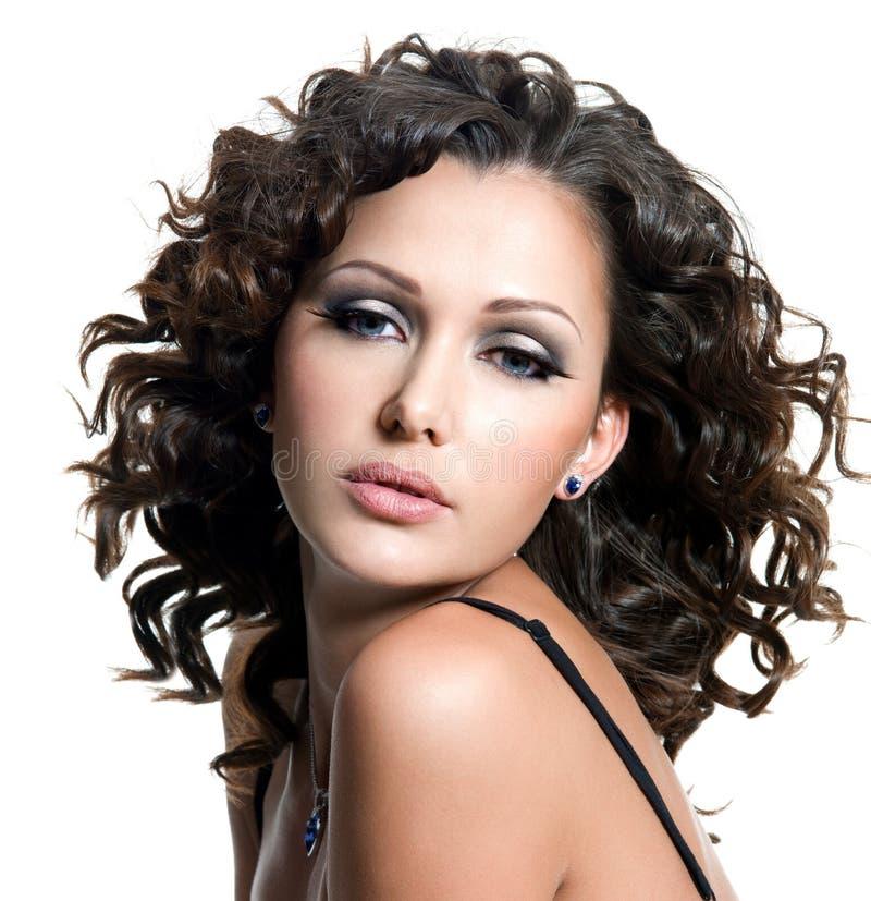 Schöne Frau mit Art und Weiseverfassung und dem lockigen Haar lizenzfreie stockbilder