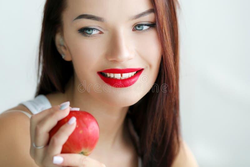Schöne Frau mit Bühnenschminken in einer weißen T-Shirt-Nähe hält frische Früchte in ihren Händen stockbild