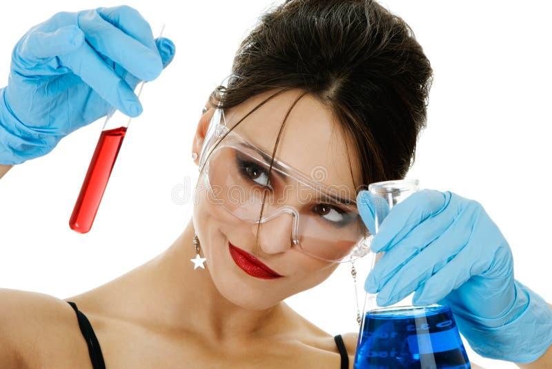 Schöne Frau mit chemischen Glaswaren lizenzfreie stockbilder