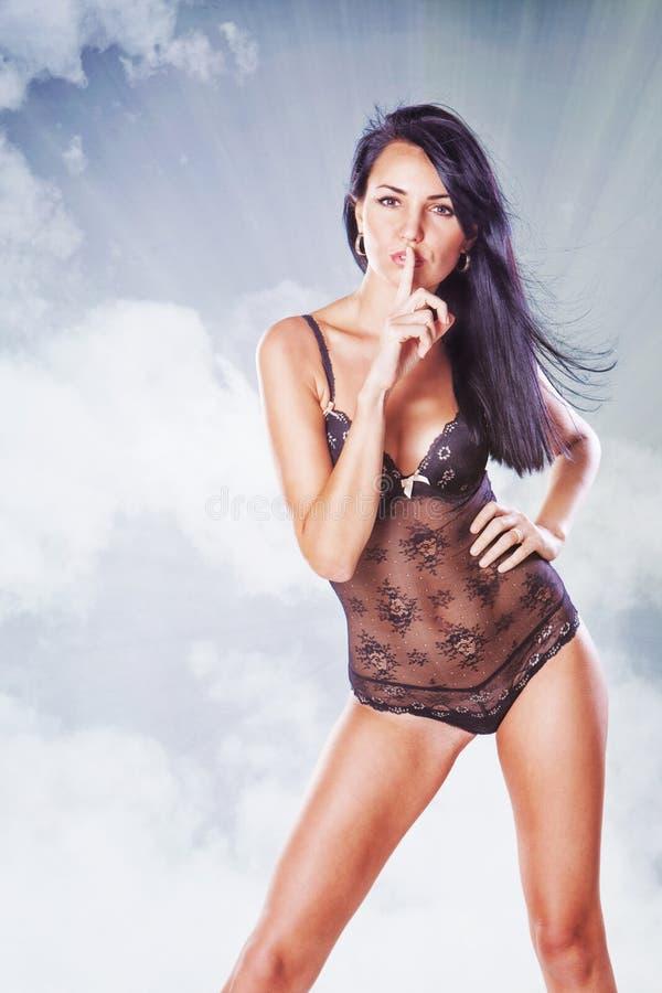 Schöne Frau mit dem Finger auf ihren Lippen in Unterwäsche copyspace s lizenzfreie stockfotografie