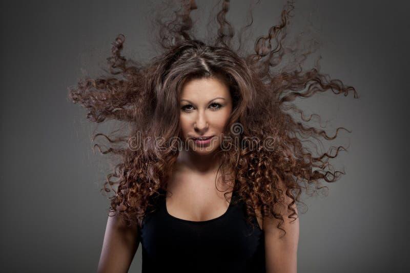 Schöne Frau mit dem lockigen Haar in einer Luft stockbilder