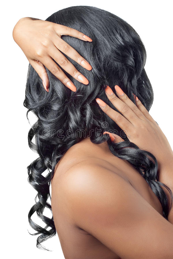 Schöne Frau mit den Händen auf ihrem lockigen Haar stockfotos