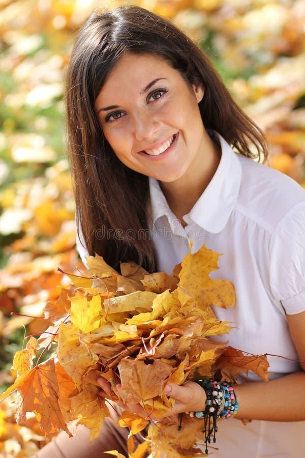 Schöne Frau mit einem Blumenstrauß der Ahornblätter stockbilder